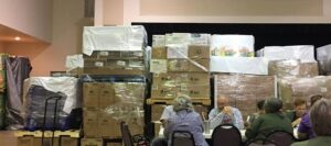 People sitting in front of pallets of emergency supplies